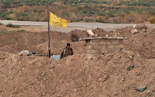 A soldier from the Syrian Democratic Forces, SDF, stands guard at the Syrian side of the border with Iraq near Rabiaa border crossing, Iraq, Wednesday, Oct. 16, 2019. Najah al-Shammari, Iraq's defense minister said that some members of the Islamic State group were able to flee northern Syria and cross into Iraq. The Iraqi official added that some of them are still at large while others were detained. (AP Photo/Hadi Mizban)