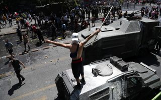 A demonstrator gestures on top of an armored vehicle during a protest against Chile's state economic model in Santiago, Chile October 23, 2019. REUTERS/Ivan Alvarado