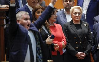 Romanian Prime Minister Viorica Dancila, right, watches as an opposition lawmaker flashes victory signs after casting his vote during a no confidence vote in Bucharest, Romania, Thursday, Oct. 10, 2019. Romania's Social Democrat government has lost a vote of no-confidence in Parliament. (AP Photo/Vadim Ghirda)