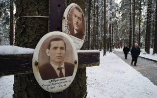 People walk past portraits of victims hanging on trees, as people gather to commemorate victims of Soviet repressions during the Great Terror, the Soviet dictator Joseph Stalin's purges, at Levashovo Memorial cemetery on the outskirts of St.Petersburg, Russia, Wednesday, Oct. 30, 2019. About 45,000 of the executed were buried in the Levashovo cemetery in 1937-1953, and October 30 is the Day of Remembrance for the Victims of Political Repressions in Russia. (AP Photo/Dmitri Lovetsky)