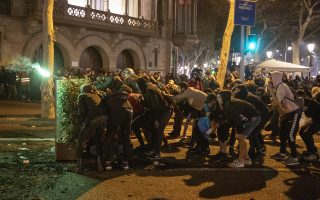 Protestors take cover during clashes with police in Barcelona, Spain, Friday, Oct. 18, 2019. Catalonia's separatist leader vowed Thursday to hold a new vote to secede from Spain in less than two years as the embattled northeastern region grapples with a wave of violence that has tarnished a movement proud of its peaceful activism. (AP Photo/Emilio Morenatti)