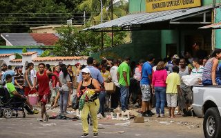 People carry goods taken from a supermarket after it was broken into, in Ciudad Bolivar, Venezuela December 17, 2016. REUTERS/William Urdaneta EDITORIAL USE ONLY. NO RESALES. NO ARCHIVE. - RTX2VHL8