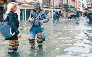 Tουρίστες στους πλημμυρισμένους, για ακόμη μία φορά, δρόμους της Βενετίας, μιας πόλης χτισμένης πάνω σε 118 νησιά. EPA/EMILIANO CRESPI