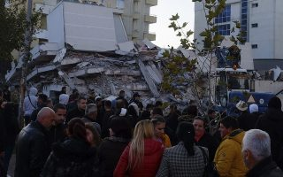 People stand near a damaged building after a magnitude 6.4 earthquake in Durres, western Albania, Tuesday, Nov. 26, 2019. A strong earthquake has shaken Albania, killing at least four people, injuring 150 and collapsing buildings. (AP Photo/Hektor Pustina)