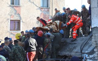Military and emergency personnel carry an injured man on a stretcher near a damaged building in Thumane, after an earthquake shook Albania, November 26, 2019. REUTERS/Flatos Bytyci