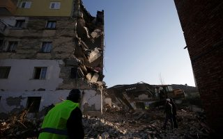 Emergency personnel stand near a damaged building in Thumane, after an earthquake shook Albania, November 26, 2019. REUTERS/Florian Goga