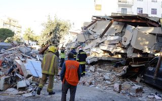 Firefighters stand next to a damaged building after a magnitude 6.4 earthquake in Durres, western Albania, Tuesday, Nov. 26, 2019. A strong earthquake has shaken Albania, killing at least four people, injuring 150 and collapsing buildings. (AP Photo/Hektor Pustina)