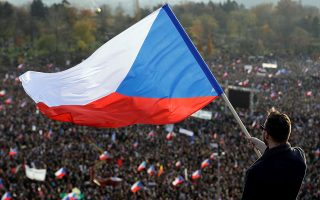 A man waves the Czech flag as demonstrators attend an anti-government rally, organised by Million Moments for Democracy, a day ahead of the 30th anniversary of the 1989 Velvet Revolution that led to the fall of Communism in former Czechoslovakia, in Prague, Czech Republic November 16, 2019. REUTERS/David W Cerny