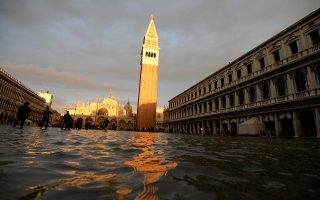 epa08004151 Tourists are seen in flooded St. Mark's Square in Venice, northern Italy, 17 November 2019. Five days ago, the Italian lagoon city experienced its worst flooding in more than 50 years.  EPA/ANDREA MEROLA