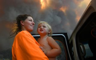 epaselect epa07992061 old daughter Charlotte look on as thick smoke rises from bushfires near Nana Glen, New South Wales, Australia, 12 November 2019 issued 13 November 2019). There are more than 50 fires burning around the state of New South Wales, with about half of those uncontained.  EPA/DAN PELED AUSTRALIA AND NEW ZEALAND OUT