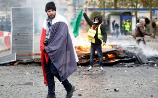 A man draped in a French national flag walks next to a burning roadblock during a demonstration to mark the first anniversary of the