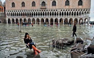 Τίποτα δεν μπορεί να κάμψει τη βούληση των επισκεπτών της Βενετίας, όπως αποδεικνύει η γυναίκα που κάθεται στην πλημμυρισμένη πλατεία του Αγίου Μάρκου. Δύο άτομα έχασαν τη ζωή τους από τη θεομηνία, ενώ σημαντικές ζημιές υπέστη και η βασιλική του Αγίου Μάρκου, που πλημμύρισε.