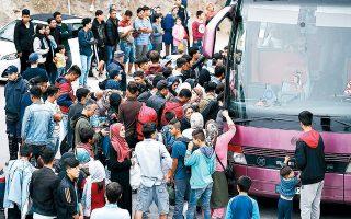 Πρόσφυγες και μετανάστες ετοιμάζονται να αναχωρήσουν από το ΚΥΤ Μόριας. Στόχος της κυβέρνησης είναι η μεταφορά 20.000 ατόμων από τα νησιά προς την ενδοχώρα έως το τέλος του έτους.