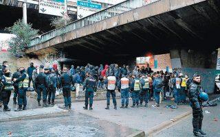 Αστυνομικοί φρουρούν μετανάστες κατά την επιχείρηση στο Πορτ ντε λα Σαπέλ, όπου ζούσαν σε σκηνές –κάτω από γέφυρες του περιφερειακού αυτοκινητοδρόμου– 1.200 με 1.300 άτομα, στην πλειονότητά τους άνδρες.