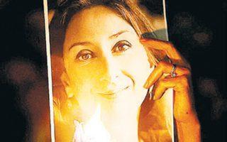 Μαλτέζος κρατάει πορτρέτο της δημοσιογράφου σε ολονυχτία στη Βαλέτα, λίγο μετά τη δολοφονία της.
