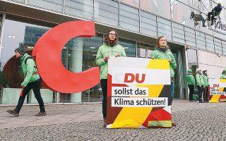 To C, μεταφερμένο από τα κεντρικά γραφεία του CDU, στο Βερολίνο, στην... πλάτη Γερμανού ακτιβιστή. «ΕΣΥ πρέπει να προστατεύσεις το κλίμα», αναφέρει το λογοπαίγνιο της Greenpeace.