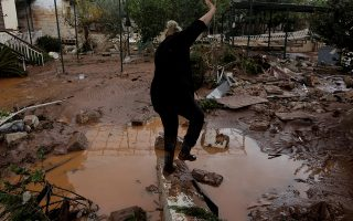 A local stumbles as she walks on debris in a yard, following a heavy rainfall in the town of Mandra. REUTERS/Alkis Konstantinidis