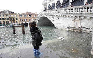 A woman looks at the Rialto Bridge during high water, in Venice, Wednesday, Nov. 13, 2019. The high-water mark hit 187 centimeters (74 inches) late Tuesday, Nov. 12, 2019, meaning more than 85% of the city was flooded. The highest level ever recorded was 194 centimeters (76 inches) during infamous flooding in 1966. (AP Photo/Luca Bruno)