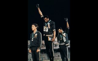 Οι Τόμι Σμιθ και Τζον Κάρλος με υψωμένη τη γροθιά και φορώντας ένα μαύρο γάντι στους Ολυμπιακούς Αγώνες του Μεξικού, το 1968. ASSOCIATED PRESS