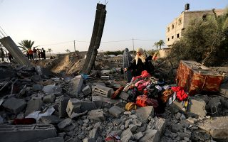 A Palestinian woman inspects a house destroyed in an Israeli air strike in the southern Gaza Strip November 13, 2019. REUTERS/Ibraheem Abu Mustafa