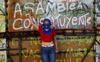A demonstrator poses for a portrait in front of a graffiti reading