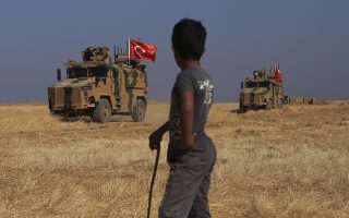 A Turkish n armored vehicles patrol as they conduct a joint ground patrol with American forces in the so-called