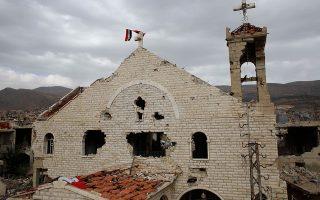 Συριακές σημαίες έχουν τοποθετηθεί στον ακρωτηριασμένο σταυρό, στην κορυφή κατεστραμμένης εκκλησίας σε προάστιο της Δαμασκού. Οι χριστιανικοί πληθυσμοί δοκιμάζονται στις χώρες της Μέσης Ανατολής και το μέλλον τους, σύμφωνα με τους δύο καθηγητές που μιλούν στην «Κ», δεν είναι ευοίωνο. A.P./Hassan Ammar