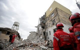 Emergency personnel stand on debris of collapsed and damaged buildings following Tuesday's powerful earthquake in Thumane, Albania, November 27, 2019. REUTERS/Florion Goga