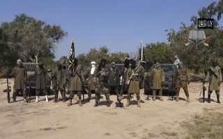 """FILE - In this file image taken from video released late Friday evening, Oct. 31, 2014, by Boko Haram, Abubakar Shekau, centre, the leader of Nigeria's Islamic extremist group. Nigeria's Boko Haram Islamic extremists have a new leader who promises to end attacks on mosques and markets used by Muslims, according to an interview published Wednesday, Aug. 3, 2016 by the Islamic State. The group's newspaper al-Nadaa identifies Abu Musab al-Barnawi as the new """"Wali"""" of its West Africa Province _ a title previously used to describe long-time leader Abubakar Shekau. (Boko Haram, via AP, File)"""