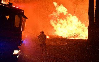 epa08042709 A firefighter works as a fire encroaches on properties near Termeil, New South Wales, Australia, 03 December 2019 (issued 04 December 2019). According to media reports, more than 100 fires were burning across the state of New South Wales on 03 December, with more than 50 of them still uncontained.  EPA/DEAN LEWINS  AUSTRALIA AND NEW ZEALAND OUT