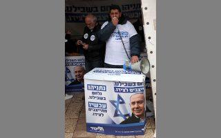 Ισραηλινοί υποστηρικτές της υποψηφιότητας Νετανιάχου, σε προεκλογικό περίπτερο σε δρόμο της Ιερουσαλήμ, την Πέμπτη.
