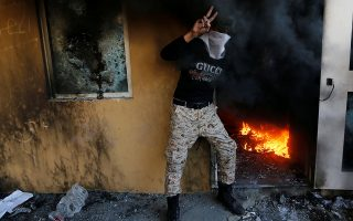 A member of Hashd al-Shaabi (paramilitary forces) flashes the victory sign as he stands next to a reception room of the U.S. Embassy with fire, during a protest to condemn air strikes on bases belonging to Hashd al-Shaabi (paramilitary forces), in Baghdad, Iraq December 31, 2019. REUTERS/Wissm al-Okili