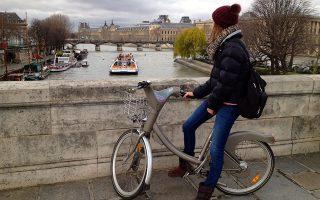 Τη γέφυρα των Τεχνών παρατηρεί η ποδηλάτισσα στο Παρίσι, που ενοικίασε ποδήλατο Velib.