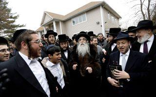Υπερορθόδοξοι Εβραίοι συγκεντρωμένοι έξω από το σπίτι του ραββίνου Τσάιμ Ρότενμπεργκ (κέντρο), στο Μόνσεϊ της Νέας Υόρκης, στο οποίο ένας άνδρας εισέβαλε κρατώντας σπαθί και τραυμάτισε πέντε ανθρώπους. EPA/PETER FOLEY