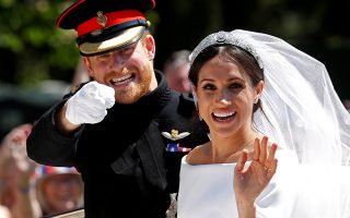 FILE PHOTO: Britain's Prince Harry gestures next to his wife Meghan as they ride a horse-drawn carriage after their wedding ceremony at St George's Chapel in Windsor Castle in Windsor, Britain, May 19, 2018. REUTERS/Damir Sagolj/File Photo