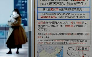 A woman wearing a mask walks past a quarantine notice about the outbreak of coronavirus in Wuhan, China at an arrival hall of Haneda airport in Tokyo, Japan, January 20, 2020. REUTERS/Kim Kyung-Hoon