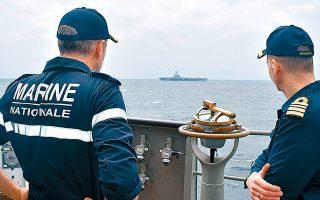 Ο υποναύαρχος Μαρκ Οσεντά, διοικητής της Ναυτικής Δύναμης 473 που συνοδεύει το «Σαρλ ντε Γκωλ», παρατηρεί το γαλλικό αεροπλανοφόρο από το κατάστρωμα της φρεγάτας «Σπέτσαι» με τον κυβερνήτη του πλοίου, αντιπλοίαρχο Παναγιώτη Κατωπόδη, πριν από λίγες ημέρες στα δυτικά της Κρήτης.