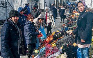 Πρόσφυγες και μετανάστες αγοράζουν φρούτα και λαχανικά σε αυτοσχέδια αγορά  στον προσφυγικό καταυλισμό της Μόριας. Tη σωστή λειτουργία του ΚΥΤ προτείνει ως λύση ο δήμαρχος της Λέσβου.