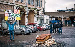 Γάλλος ακτιβιστής κραδαίνει πανό με το σύνθημα «Μακρόν, φύγε εσύ και η μεταρρύθμισή σου», έξω από σιδηροδρομικό σταθμό του Παρισιού.