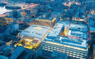 Στη φωτογραφία τα τρία κτίρια γραφείων (φωταγωγημένα δεξιά) που ανακατασκεύασε η εταιρεία ανάπτυξης ακινήτων Dimand Real Estate στην περιοχή του Αγίου Διονυσίου. Σημείο αναφοράς του επενδυτικού σχεδίου είναι οι πρώην εγκαταστάσεις της καπνοβιομηχανίας «Παπαστράτος».