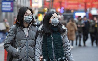 epa08155268 People wear face masks in London, Britain, 23 January 2020. British Health Secretary Matt Hancock has stated that the Corona virus may already be in Britain.  EPA/ANDY RAIN