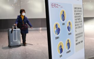 epa08175880 A woman wearing a face masks walks past a coronavirus healthcare notice at Heathrow Airport in London, Britain, 29 January 2020. British Airways has announced it has suspended all flights to and from mainland China due to the threat of the coronavirus. Flights from the virus hit areas within China may begin bringing home Britons this coming Thursday.  EPA/ANDY RAIN