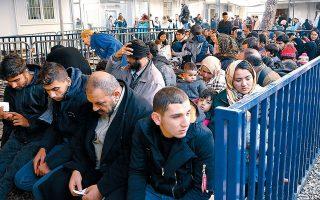 Νεοαφιχθέντες πρόσφυγες και μετανάστες περιμένουν να εξεταστούν από τους αρμοδίους στο ΚΥΤ της Μόριας.