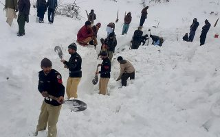 Police officers and local residents dig to search bodies of victims of avalanches in Doodnail village in Neelum Valley, Pakistan-administered Kashmir, Wednesday, Jan. 15, 2020. Search teams aided by Pakistani troops pulled out 21 more bodies from homes destroyed by this week's avalanches in the disputed Himalayan region of Kashmir, raising the overall death toll due to severe winter weather to more than 155 for Pakistan and Afghanistan, officials said. (AP Photo/Abdul Razaq)