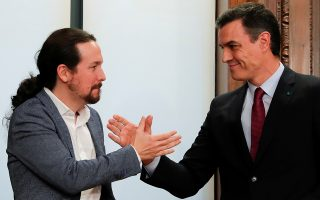 FILE PHOTO: Spain's acting Prime Minister Pedro Sanchez and Unidas Podemos (Together We Can) leader Pablo Iglesias shake hands as they present their coalition agreement at Spain's Parliament in Madrid, Spain, December 30, 2019. REUTERS/Susana Vera/File Photo