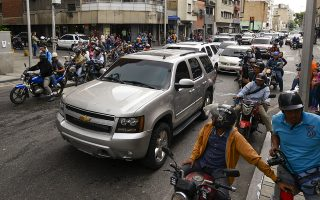 Journalists on motorbikes follow a caravan of opposition lawmakers on their way to the National Assembly in Caracas, Venezuela, Wednesday, Jan. 15, 2020. The caravan returned to an opposition headquarter after government supporters hurl stones at the vehicles. (AP Photo/Matias Delacroix)