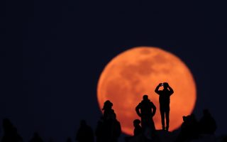 Φόντο. Πάνω στο λόφο του Αρείου Πάγου, τουρίστες και ντόπιοι φωτογραφίζουν την φωτισμένη Αθήνα και την Ακρόπολη. Πίσω τους το ολόγιομο φεγγάρι που ξεπρόβαλε στον Αττικό ουρανό αποτέλεσε το ιδανικό φόντο για την δική τους φωτογραφία.  REUTERS/Alkis Konstantinidis