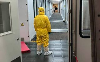 A worker in protective gear looks down the the walkway to a cargo plane, chartered by the U.S. State Department to evacuate Americans and Canadians from China due to the outbreak of novel Coronavirus, is parked next to a terminal at Wuhan Tianhe International Airport in Wuhan, China February 7, 2020.  Courtesy of Edward Wang via REUTERS. THIS IMAGE HAS BEEN SUPPLIED BY A THIRD PARTY. MANDATORY CREDIT