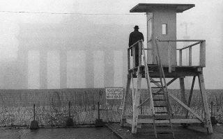 25 Νοεμβρίου 1961. Η Πύλη του Βραδεμβούργου τυλιγμένη στην ομίχλη, καθώς ένας άνδρας κοιτάζει από δυτικογερμανικό φυλάκιο πάνω από το Τείχος. H μητέρα του Λεό υπήρξε πιστό μέλος του Κόμματος, ο πατέρας του ατίθασος καλλιτέχνης. Ο ένας παππούς του ήταν  στη γαλλική αντίσταση, ο άλλος ναζιστής. A.P./HEINRICH SANDEN SR.