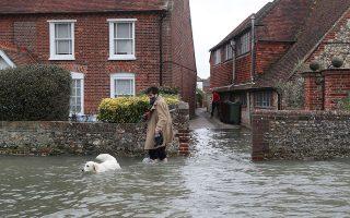 Ενας άνδρας περπατάει με τον σκύλο του σε πλημμυρισμένο δρόμο του Σάσεξ στην Αγγλία μετά το πέρασμα της «Κιάρα».